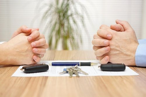 Pair of hands folded across from each other, resting on a table with a document, pen, car keys and key fobs.